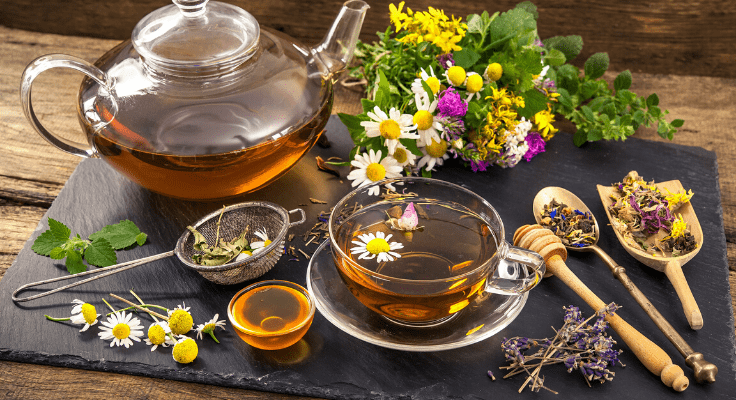 glass teapot and tea cap with herbal tea with a daisies bouquet