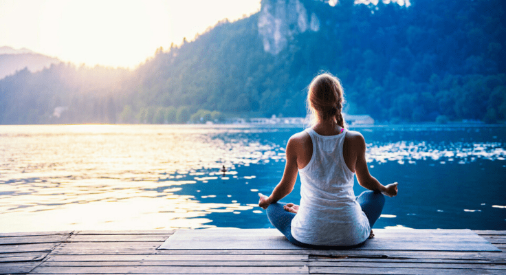woman relaxing and meditation during sunset at the waterfront