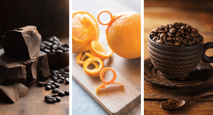 coffee beans in brown ceramic cup, orange and pieces of dark chocolate