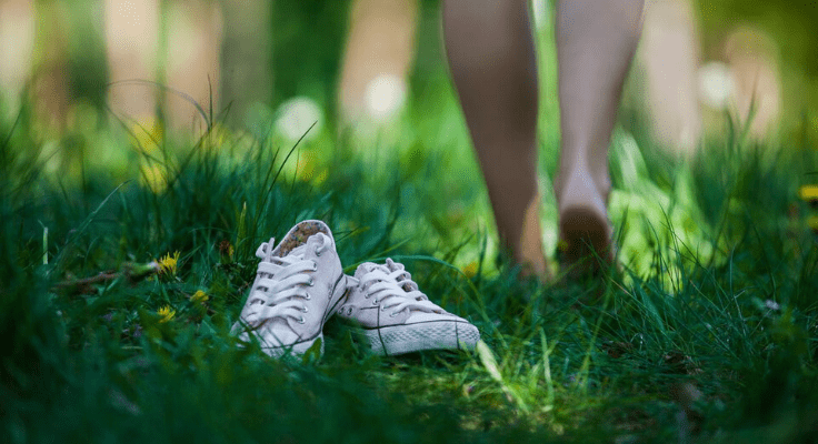 white shoes on the grass and woman walking barefoot away from them