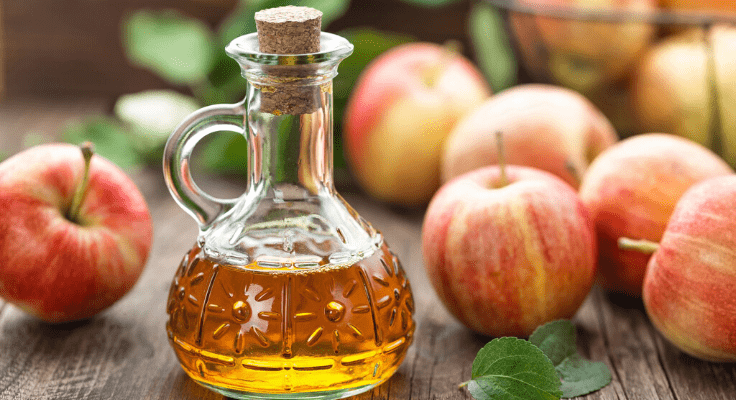 apple cider vinegar in glass decanter and apples on the table