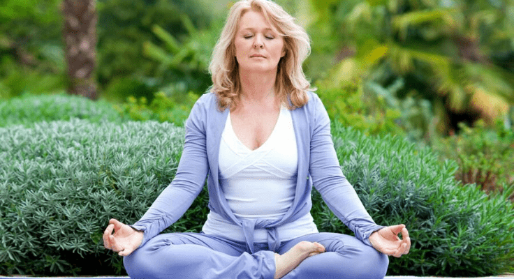 blond woman in lavender clothes meditating in the garden