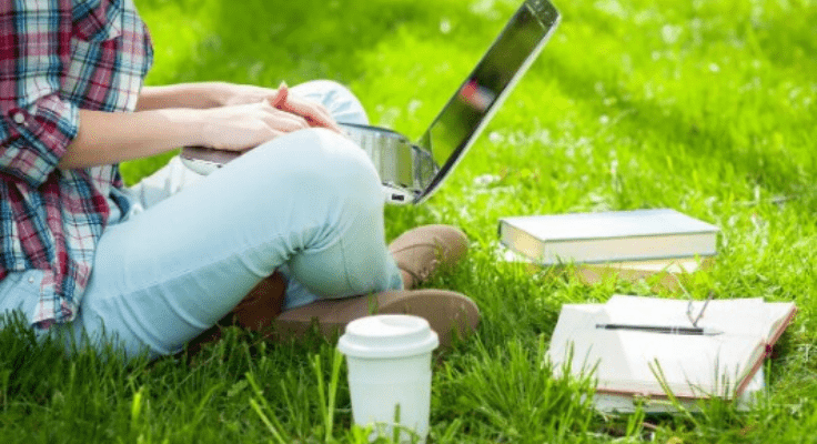 person sitting on the grass with computer and a cup of coffee