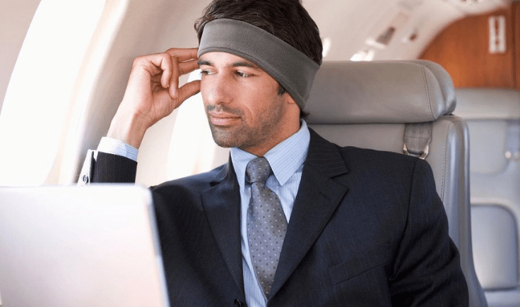 a man is flying in an airplane with sleepphones